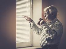 Senior man looking through jalousie Stock Photos