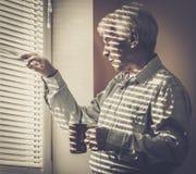 Senior man looking through jalousie. Senior man with cup looking out the window through jalousie Royalty Free Stock Image