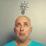 Senior man looking at light bulb Royalty Free Stock Photo