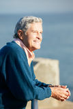 Senior Man Looking Over Railing At Sea Royalty Free Stock Photo