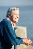 Senior Man Looking Over Railing At Sea. Smiling Royalty Free Stock Photo