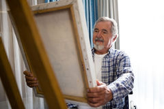 Senior man looking at painting while sitting on wheelchair Stock Photos