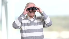 Senior man looking through a pair of binoculars. Grandfather looking into binoculars and looking for something, blurred background stock footage