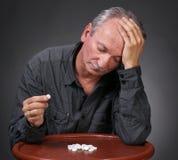 Senior man looking at pills Stock Photos