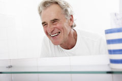 Senior Man Looking At Reflection In Bathroom Mirror Royalty Free Stock Image