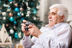 Senior man looking at retro style camera Stock Photo
