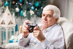 Senior man looking at retro style camera Stock Images