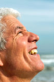 Senior man looking into the sun. Senior man is looking up into the sun, smiling. Ocean in background Royalty Free Stock Photo
