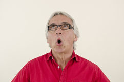 Senior man looking surprised upwards Stock Photo