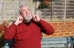 Senior man looking up with fingers in his ears. Noise. A senior man sitting outside looking up with his fingers in his ears. Protecting his ears from the loud royalty free stock photos
