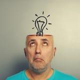Senior man looking up at light bulb. Amazed senior man looking up at light bulb in the head. photo over grey background Stock Photography