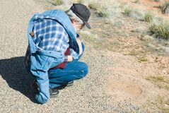 Senior Man Looks at an anthill. Senior man with a denim jacket and a cap pauses on a hike to examine an anthill Stock Photo