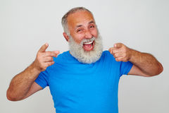 Senior man looks delighted against white background. Senior man with white beard in bright blue T-shirt looks delighted against white background stock image