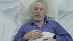 Senior man loudly snoring and puffing in bed, sleeping problems at old age