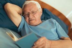 Senior man lying on bad and reading book Stock Photo