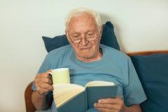 Senior man lying on bad and reading book Stock Photos