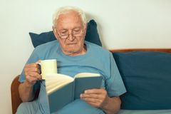 Senior man lying on bad and reading book Stock Images