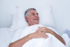 Senior man lying on bed. Happy senior man lying on bed in hospital Royalty Free Stock Photos