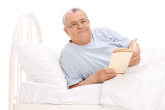 Senior man lying in bed and holding a book Royalty Free Stock Photos