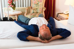 Senior man lying on the bed in the hotel room Stock Photo