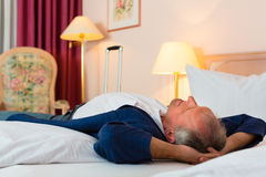 Senior man lying on the bed in the hotel room Stock Photos