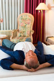 Senior man lying on the bed in the hotel room Stock Images