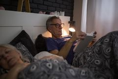 Senior man lying in bed reading book. Portrait of senior men lying in bed reading book Royalty Free Stock Photography