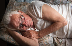 Old man lying in bed. Senior man lying in bed with reading glasses. Resting, insomnia and depression concept Royalty Free Stock Image
