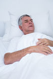 Senior man lying on bed. Unhappy senior man lying on bed in hospital Stock Image