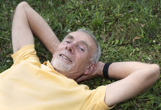 Senior man lying on grass contented Stock Photo