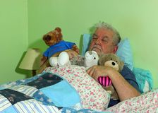 Senior man asleep in bed with soft cuddly toys. stock image