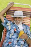 Senior Man lying on lawn chair Holding Orange Juice elevated view portrait. Royalty Free Stock Photos