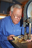 Senior Man Machining Clock Parts. A senior man working on a machine making parts to a clock royalty free stock images