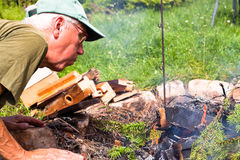 Senior man making bonfire Stock Photos