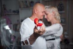 Senior man making proposal to older woman; stock photography