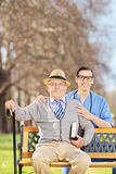 Senior man and a male nurse posing on a bench Royalty Free Stock Photography