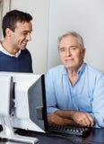 Senior Man With Male Teacher In Computer Class Stock Photos