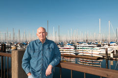 Senior Man at Marina. Casually dressed elderly man standing in front of pleasure craft and stack of colorful rental kayaks at marina, Everett, Washington, USA Royalty Free Stock Photography