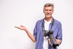 Senior man. Senior mature man is holding camera while standing against grey background stock photos
