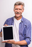 Senior man. Senior mature man is showing digital tablet and smiling while standing against grey background royalty free stock image
