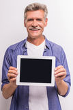 Senior man. Senior mature man is showing digital tablet and smiling while standing against grey background stock photo