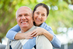 Senior man and mature woman against blured trees Royalty Free Stock Images