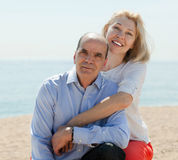 Senior man and mature woman against sea in summer Stock Photos