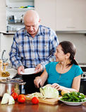 Senior man and mature  woman cooking in  kitchen Stock Image