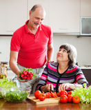 Senior man and mature woman cooking lunch stock image
