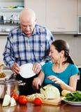 Senior man and mature  woman cooking  together Stock Photos