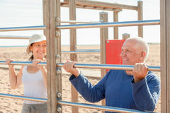 Senior man and mature woman training with pull-up bar Royalty Free Stock Image
