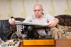 Senior Man Measuring Fabric on Sewing Machine Royalty Free Stock Photos
