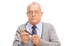 Senior man measuring his blood sugar level. Senior gentleman measuring his blood sugar level with glucometer isolated on white background Royalty Free Stock Image
