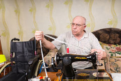 Senior Man with Measuring Tape and Sewing Machine Royalty Free Stock Photography